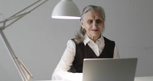 An old woman with deep wrinkles works at a laptop. Modern grandmother talks on video on the computer in the office stock footage