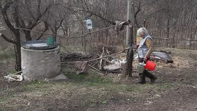 An old woman in a deserted village is gathering water from a well in a bucket, living alone. An old woman in a deserted village is gathering water from a well stock video