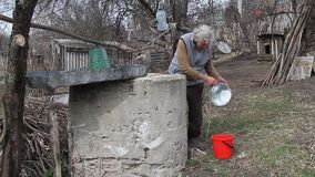 An old woman in a deserted village is gathering water from a well in a bucket, living alone. An old woman in a deserted village is gathering water from a well stock video footage