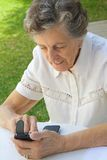An old woman in dialling a telephone number on a smartphone Stock Images