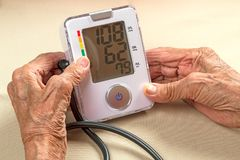 Old woman and digital blood pressure monitor Stock Photos