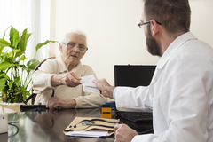 Old woman at the doctor geriatrician. geriatrician doctor with a patient in his office. The doctor gives the patient a prescription Stock Photography