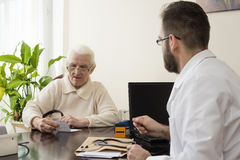 Old woman at the doctor geriatrician. geriatrician doctor with a patient in his office. Doctor`s office. A doctor takes a patient. The patient, an old women Royalty Free Stock Image