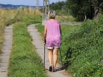 Old woman doing sports: scandinavian/nordic walking. Healthy lifestyle. A personal example of society. Healthy and active lifesty royalty free stock photo