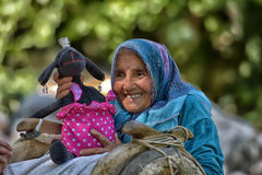 Old woman with a donkey and plaything Stock Photos