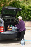 Old woman downloading the car purchase Royalty Free Stock Image