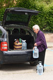 Old woman downloading the car purchase Stock Photography