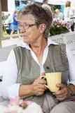 Old woman drinking coffee Royalty Free Stock Photo