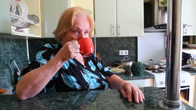 Old woman drinking cup of tea stock footage