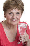 Old woman drinking glass of a mineral water Stock Image