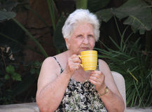 Old woman drinking tea. Portrait of an old caucasian woman drinking tea from a mug Stock Photos