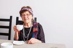 Old woman drinking tea Royalty Free Stock Photos