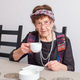 Old woman drinking tea Stock Images