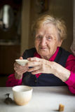 Old woman drinking tea at a table in the kitchen. Royalty Free Stock Image