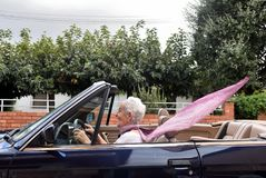 Old woman driving a convertible. Car royalty free stock image