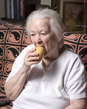 Old woman eating  bread Royalty Free Stock Image