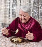Old woman eating at home Royalty Free Stock Photos