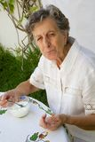 An old woman is eating a homemade yogurt. An old woman between 70 and 80 years is eating homemade yogurt at the table Royalty Free Stock Photo