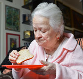 Old woman eating a slice of  bread Royalty Free Stock Photography