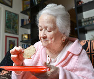 Old woman eating a slice of  bread Stock Image