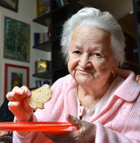 Old woman eating a slice of  bread Royalty Free Stock Images