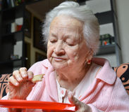 Old woman eating a slice of  bread Royalty Free Stock Photo