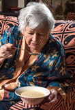Old woman eating soup Royalty Free Stock Images
