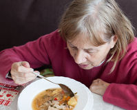 Old woman eating soup Stock Image