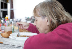 Old woman eating soup Royalty Free Stock Photography