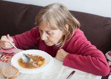 Old woman eating soup Stock Photos