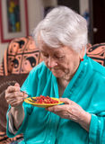 Old woman eating strawberry. At home Royalty Free Stock Image