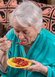 Old woman eating strawberry. At home Stock Photos