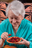 Old woman eating strawberry. At home Royalty Free Stock Photo