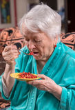 Old woman eating strawberry. At home Stock Image