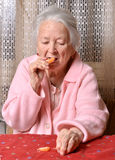 Old woman eating tangerine Royalty Free Stock Photography