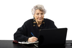 Old woman is elearning student. Old grey haired woman is elearning student with Skype Stock Photo