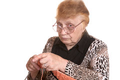 The old woman is engaged in knittin Stock Images
