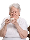 Old woman enjoying coffee or tea cup Royalty Free Stock Photo