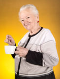 Old woman enjoying coffee or tea cup Royalty Free Stock Images