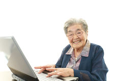 Old woman enjoys laptop computer Stock Photos