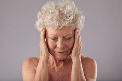 Old woman examining her skin condition Royalty Free Stock Images