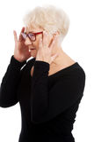 An old woman is eye glasses is having a headache. Royalty Free Stock Images