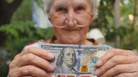 Old woman in eyeglasses showing one hundred dollar bill into camera outdoor. Happy grandmother holding foreign currency