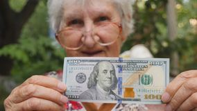 Old woman in eyeglasses showing one hundred dollar bill into camera and smiling outdoor. Happy grandmother holding