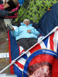 Old woman in fan camp. An old female fan of the royal wedding between Prince William and Kate Middleton. She shows the book she is reading while she is waiting Royalty Free Stock Photo