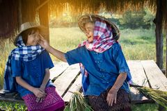 Old woman farmer and granddaughter sitting at cabin after harvesting in rice field Royalty Free Stock Photo