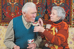 Old woman feed old man. Old woman spoon-feed old man Royalty Free Stock Photography