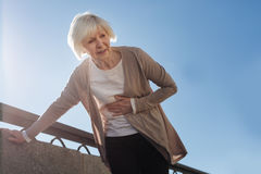 Old woman feeling stomachache outside. It can happen everywhere. Aged ill scared woman standing and feeling terrible pain in her stomach while walking on the royalty free stock photos