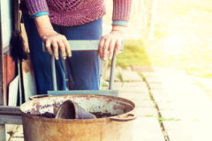 Old woman filling a pot with fresh soil. Symbol of spring Royalty Free Stock Photos
