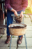 Old woman filling a pot with fresh soil. Symbol of spring Royalty Free Stock Photo